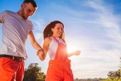 Jeune homme et femme courant sur le fond de ciel bleu Couples ayant l'amusement au coucher du soleil Vacances d'été Images stock