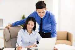 Jeune homme et femme d'affaires travaillant dans le bureau photographie stock libre de droits