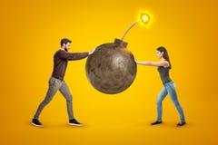 Jeune homme et femme dans des vêtements sport tenant la grande bombe de boule avec le fusible sur le fond jaune photographie stock