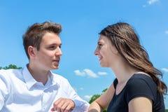 Jeune homme et femme dans l'amour conversating avec le ciel bleu Photographie stock libre de droits