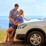 Jeune homme et femme dans la position à la voiture contre la mer Images stock