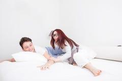 Jeune homme et femme dans le sourire de combat d'oreiller photographie stock libre de droits