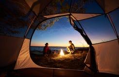 Jeune homme et femme de couples ayant le repos à la tente de touristes et au feu de camp brûlant sur le bord de mer près de la fo image stock