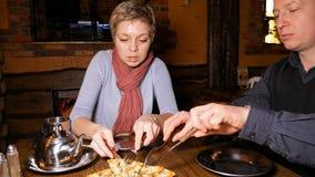 Jeune homme et femme de couples mangeant de la pizza dans un café Image libre de droits