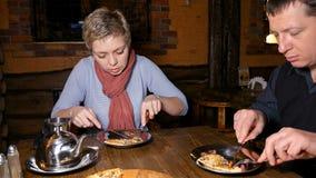 Jeune homme et femme de couples mangeant de la pizza dans un café Photographie stock