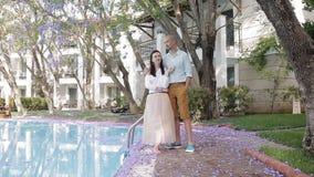 Jeune homme et femme de couples parlant dans l'arrière-cour par la piscine banque de vidéos