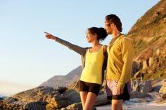 Jeune homme et femme de sourire à la plage appréciant la vue Photographie stock libre de droits