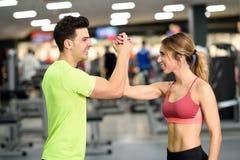 Jeune homme et femme de sourire faisant la haute cinq dans le gymnase Photos stock