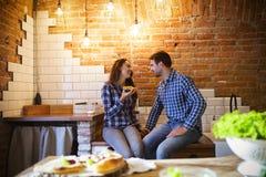 Jeune homme et femme faisant cuire et mangeant ensemble à la cuisine Photographie stock