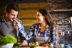 Jeune homme et femme faisant cuire et mangeant ensemble à la cuisine Images libres de droits