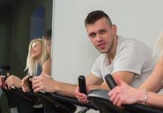 Jeune homme et femme faisant du vélo dans le gymnase, exerçant des jambes faisant les vélos de recyclage de cardio- séance d'entr Photographie stock