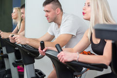 Jeune homme et femme faisant du vélo dans le gymnase, exerçant des jambes faisant les vélos de recyclage de cardio- séance d'entr Photo stock