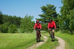 Jeune homme et femme faisant un cycle dans une nature Photo libre de droits