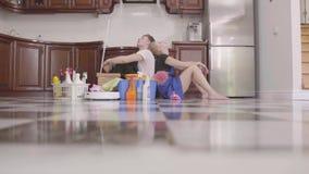 Jeune homme et femme fatigués s'asseyant sur le plancher de nouveau au dos Jour de nettoyage L'équipement de nettoyage est voisin clips vidéos