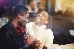 Jeune homme et femme heureux riant ensemble tout en se reposant dans le restaurant moderne pendant la pause-café, Photo stock