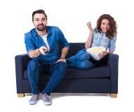 Jeune homme et femme heureux s'asseyant sur le sofa avec le maïs éclaté et la montre Photos stock