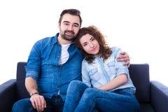 Jeune homme et femme heureux s'asseyant sur le sofa d'isolement sur le blanc Photographie stock