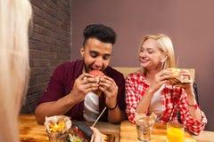 Jeune homme et femme mangeant des hamburgers d'aliments de préparation rapide se reposant au Tableau en bois en café Photographie stock