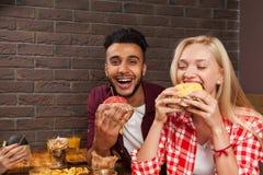 Jeune homme et femme mangeant des hamburgers d'aliments de préparation rapide se reposant au Tableau en bois en café Photo libre de droits