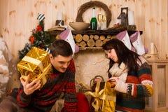 Jeune homme et femme ouvrant leurs cadeaux de Noël Photo libre de droits
