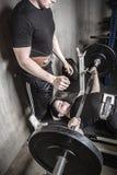 Jeune homme et femme powerlifting dans un gymnase graveleux de sous-sol image stock