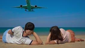 Jeune homme et femme s'étendant sur une belle plage pour observer un avion de débarquement clips vidéos
