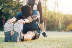 Jeune homme et femme s'étirant en parc Image libre de droits
