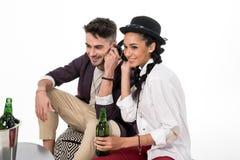 Jeune homme et femme s'asseyant à la table avec des bouteilles à bière et à la musique de écoute avec des écouteurs Images libres de droits