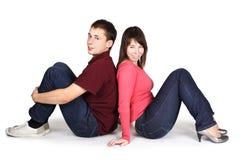 Jeune homme et femme s'asseyant de nouveau au dos Photographie stock