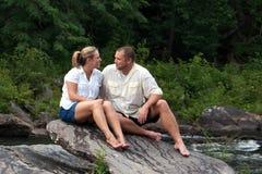 Jeune homme et femme s'asseyant sur de grandes roches en dedans  Photo stock
