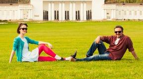 Jeune homme et femme s'asseyant sur l'herbe Photographie stock