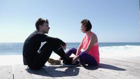 Jeune homme et femme s'asseyant sur la plage rocheuse Doigt de points d'ami vers la mer et le ciel et parler Mouvement lent clips vidéos
