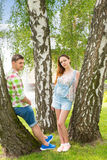 Jeune homme et femme se penchant sur des arbres en parc Photo libre de droits