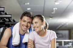 Jeune homme et femme souriant et s'asseyant ensemble au gymnase Photo stock
