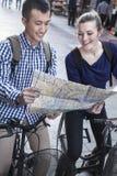 Jeune homme et femme sur des bicyclettes, regardant la carte. Photos stock