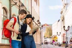 Jeune homme et fille comme deux touristes avec la ville tracent Photographie stock libre de droits