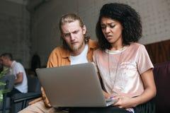 Jeune homme et fille regardant amazedly l'ordinateur portable Fille d'afro-américain avec les cheveux bouclés foncés se reposant  Images stock