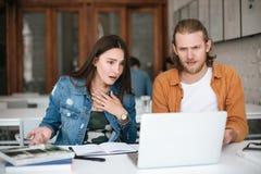 Jeune homme et fille regardant amazedly sur l'ordinateur portable tout en travaillant ensemble dans le bureau Jeunes étudiants s' Image stock