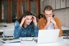 Jeune homme et fille regardant fatigué sur l'ordinateur portable tout en travaillant ensemble dans le bureau Étudiants stupéfaits Images stock