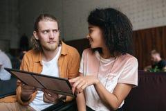Jeune homme et fille s'asseyant dans le restaurant avec le menu dans des mains Jolie fille d'Afro-américain avec les cheveux bouc Photo libre de droits