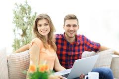 Jeune homme et fille s'asseyant devant un ordinateur portable ouvert Photographie stock libre de droits