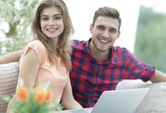 Jeune homme et fille s'asseyant devant un ordinateur portable ouvert Image stock