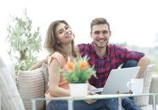 Jeune homme et fille s'asseyant devant un ordinateur portable ouvert Photos libres de droits