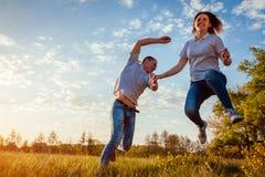Jeune homme et fonctionnement et sauter de femme Couples ayant le champ d'amusement au printemps au coucher du soleil Image libre de droits