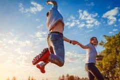 Jeune homme et fonctionnement et sauter de femme Couples ayant le champ d'amusement au printemps au coucher du soleil Photographie stock libre de droits