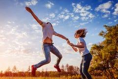 Jeune homme et fonctionnement et sauter de femme Couples ayant le champ d'amusement au printemps au coucher du soleil Types appré Photographie stock libre de droits