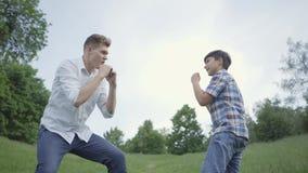Jeune homme et la boxe de garçon en parc Les jeunes poinçons d'imitation de père et son fils faisant la même chose Loisirs de fam banque de vidéos