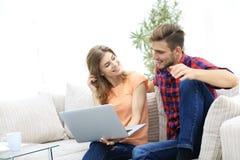 Jeune homme et son amie regardant des photos sur l'ordinateur portable Images libres de droits