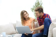 Jeune homme et son amie regardant des photos sur l'ordinateur portable Photographie stock libre de droits