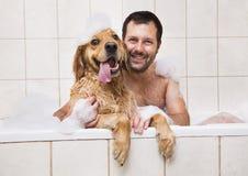 Jeune homme et son chien dans le bain moussant image stock
